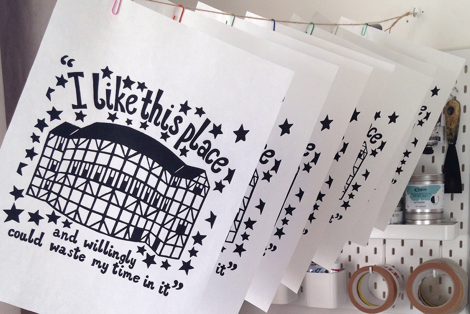A series of prints hang to dry, with an illustration of the Globe Theatre and the text: I like this place and willingly could waste my time in it