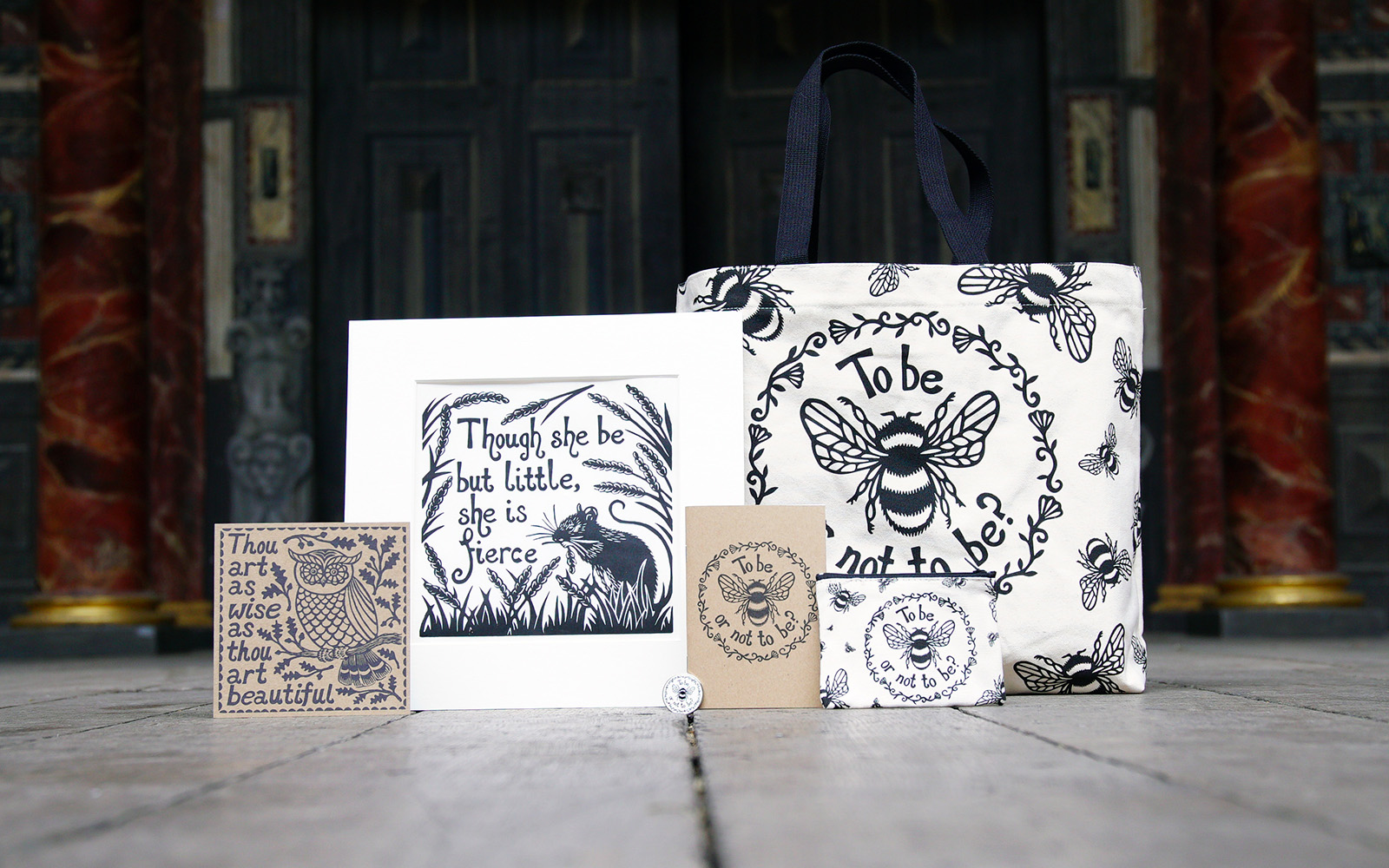 A selection of white and beige products, including a print, card, tote bag, notebook and purse, featuring a illustrative screen printing design of bees, flowers, and animals.