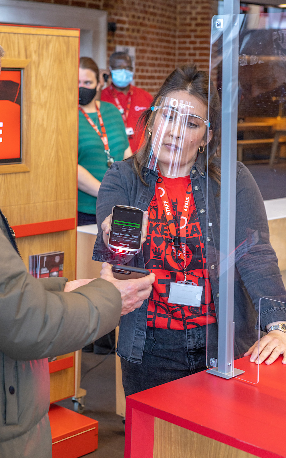 A member of staff in a visor uses a machine to scan a QR code on someone's device