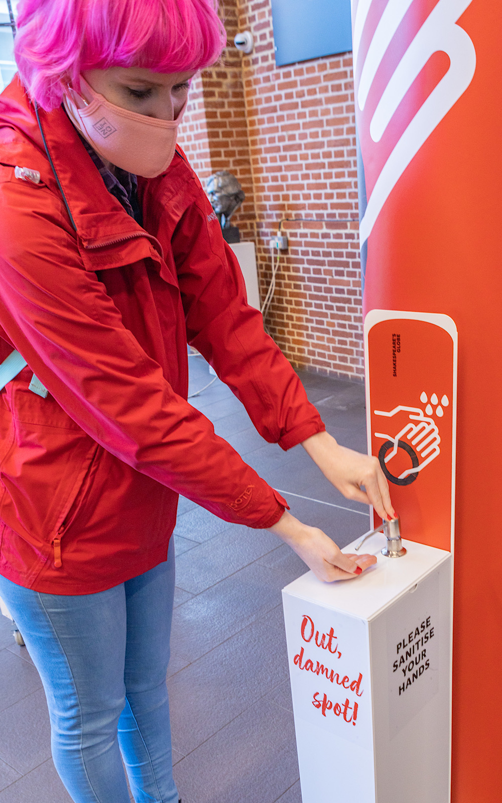 An audience member in a red jacket leans down to sanitise her hands at a sanitiser station