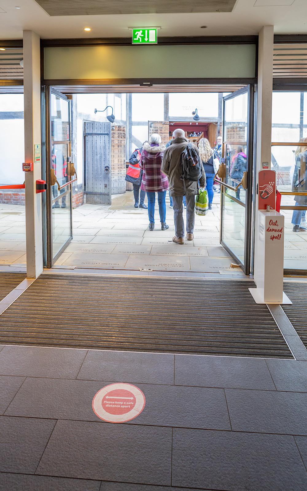 A wide, open door leads to an outdoor piazza where people are walking towards another door