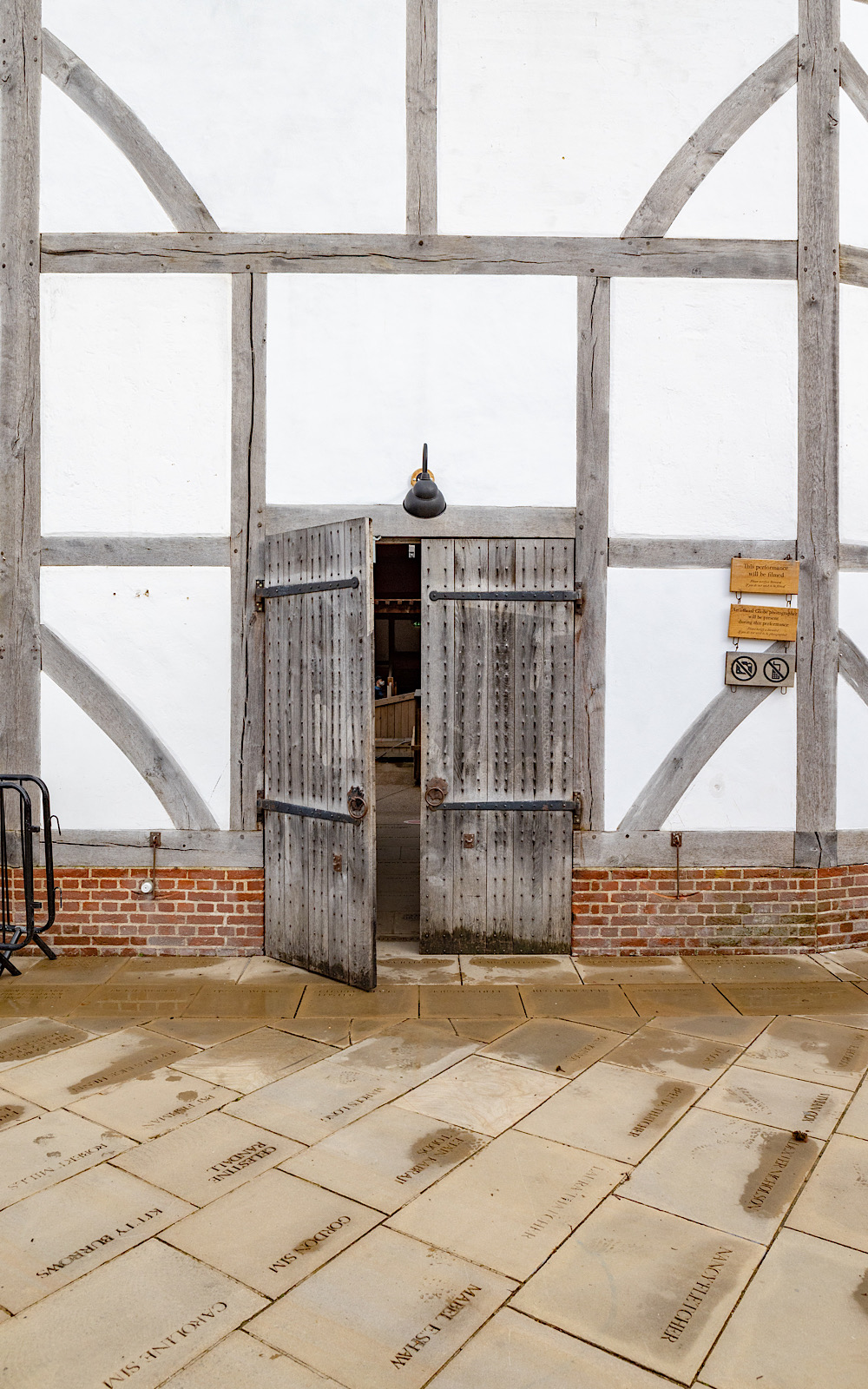 Within a white, wooden-beamed wall, a wooden pair of doors are open