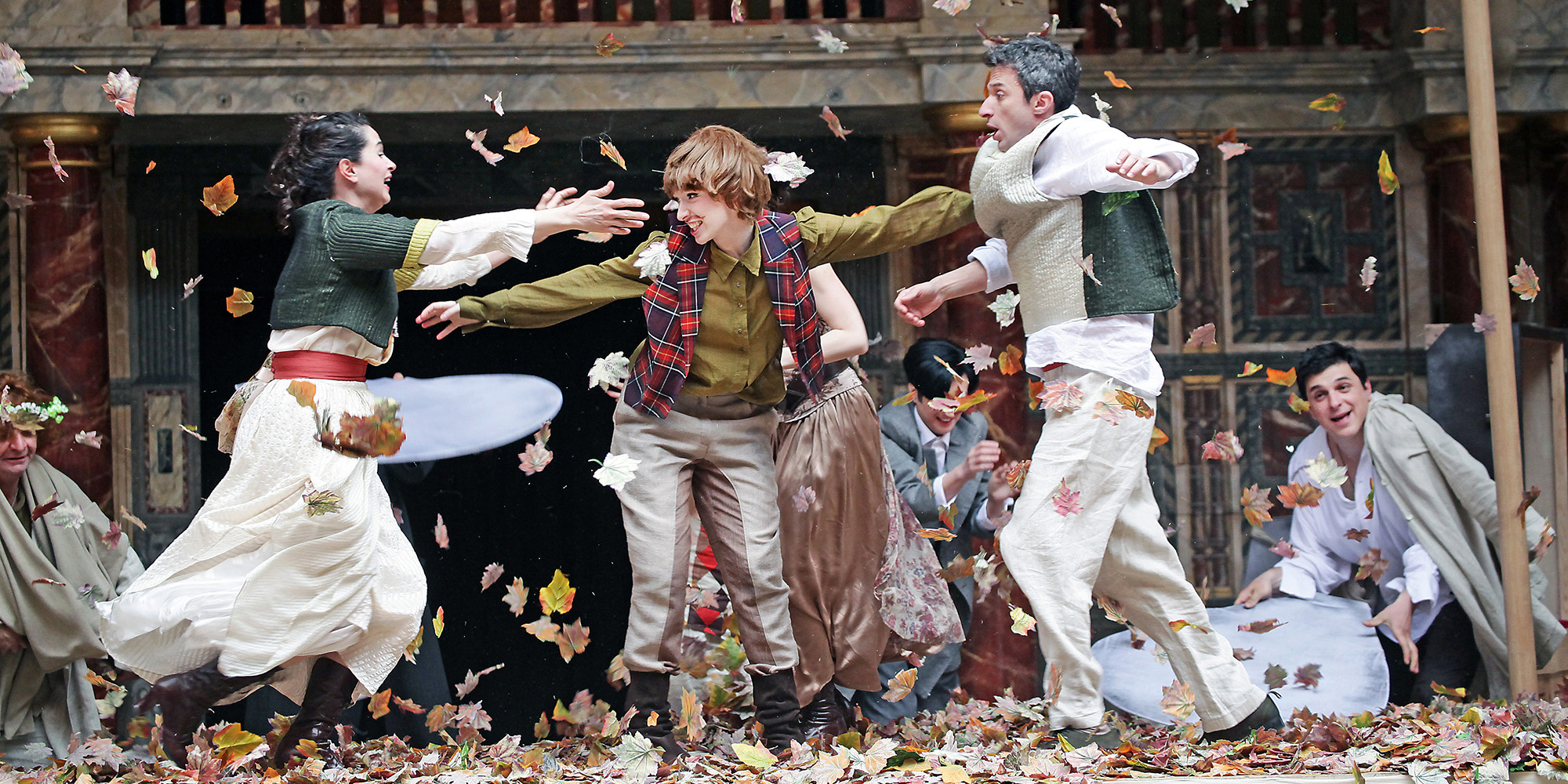 Actors on the stage that look as if they were playing in leaves