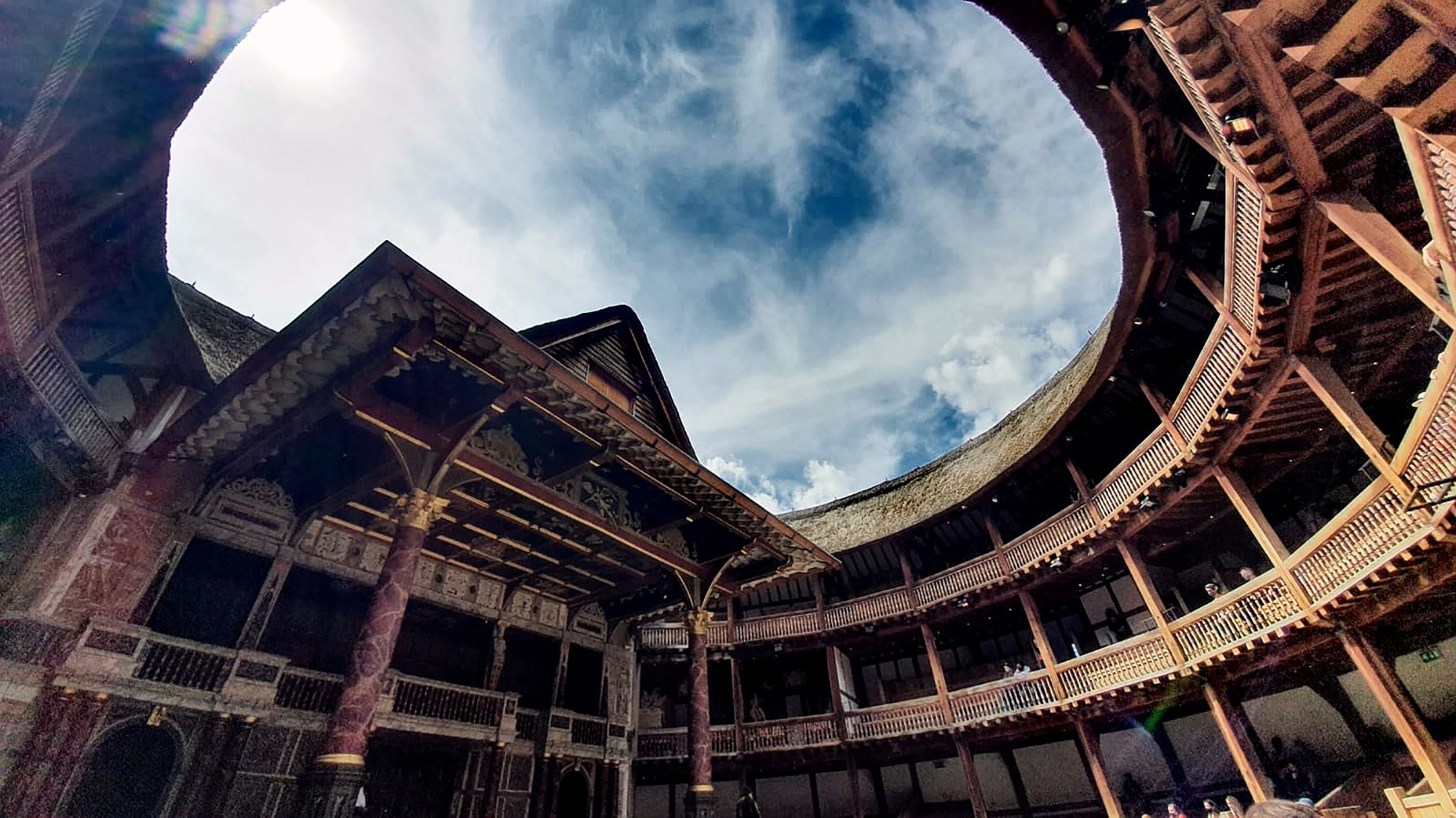 A blue sky streaked with wisps of white cloud above the circular timbre structure of the Globe Theatre.