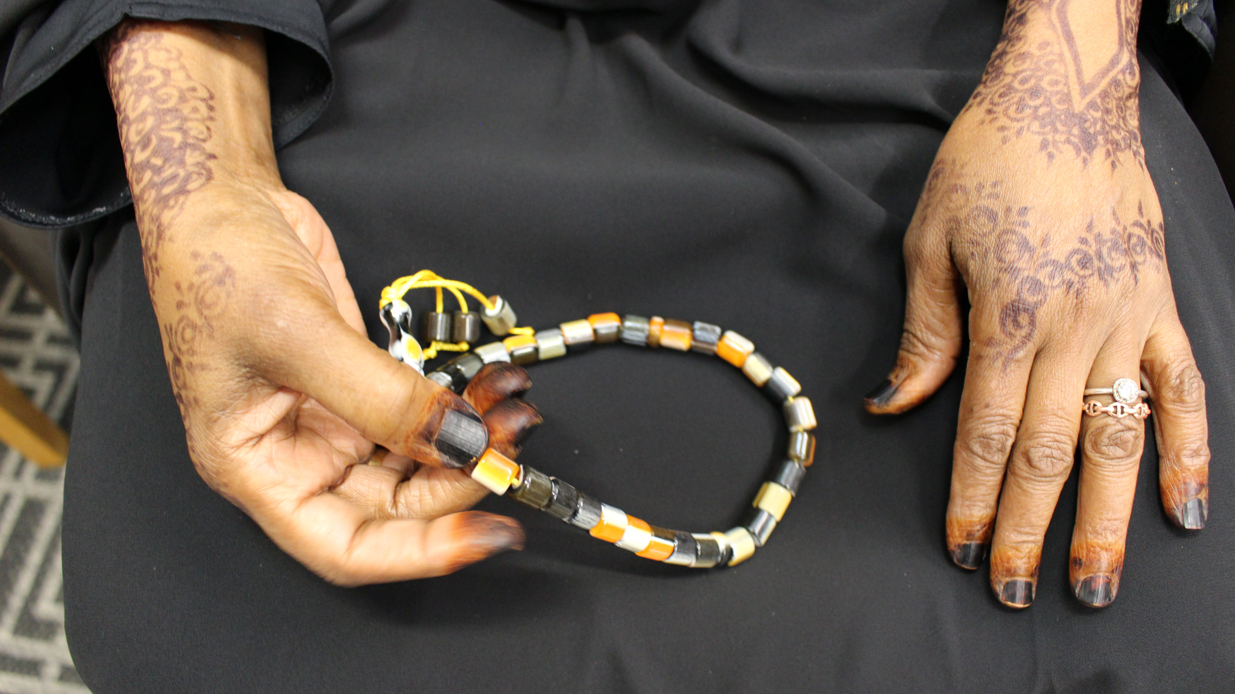 A pair of hands holds a black, orange and white beaded necklace