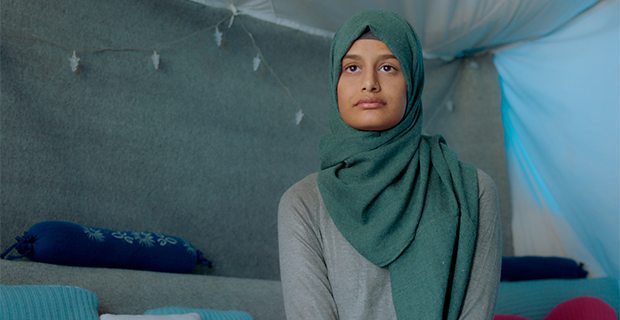A young woman in a hijab sitting in a tent stares into the camera.
