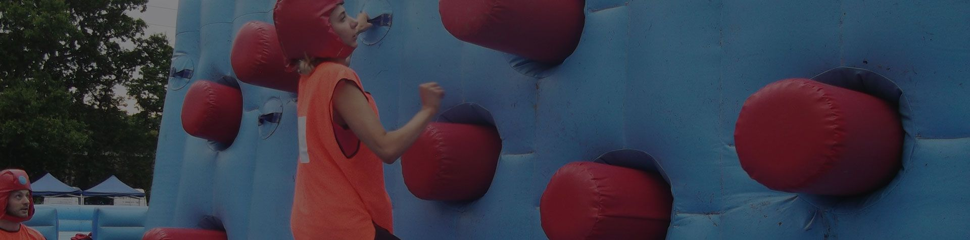 girl trying to get across Totally Wiped Out inflatable