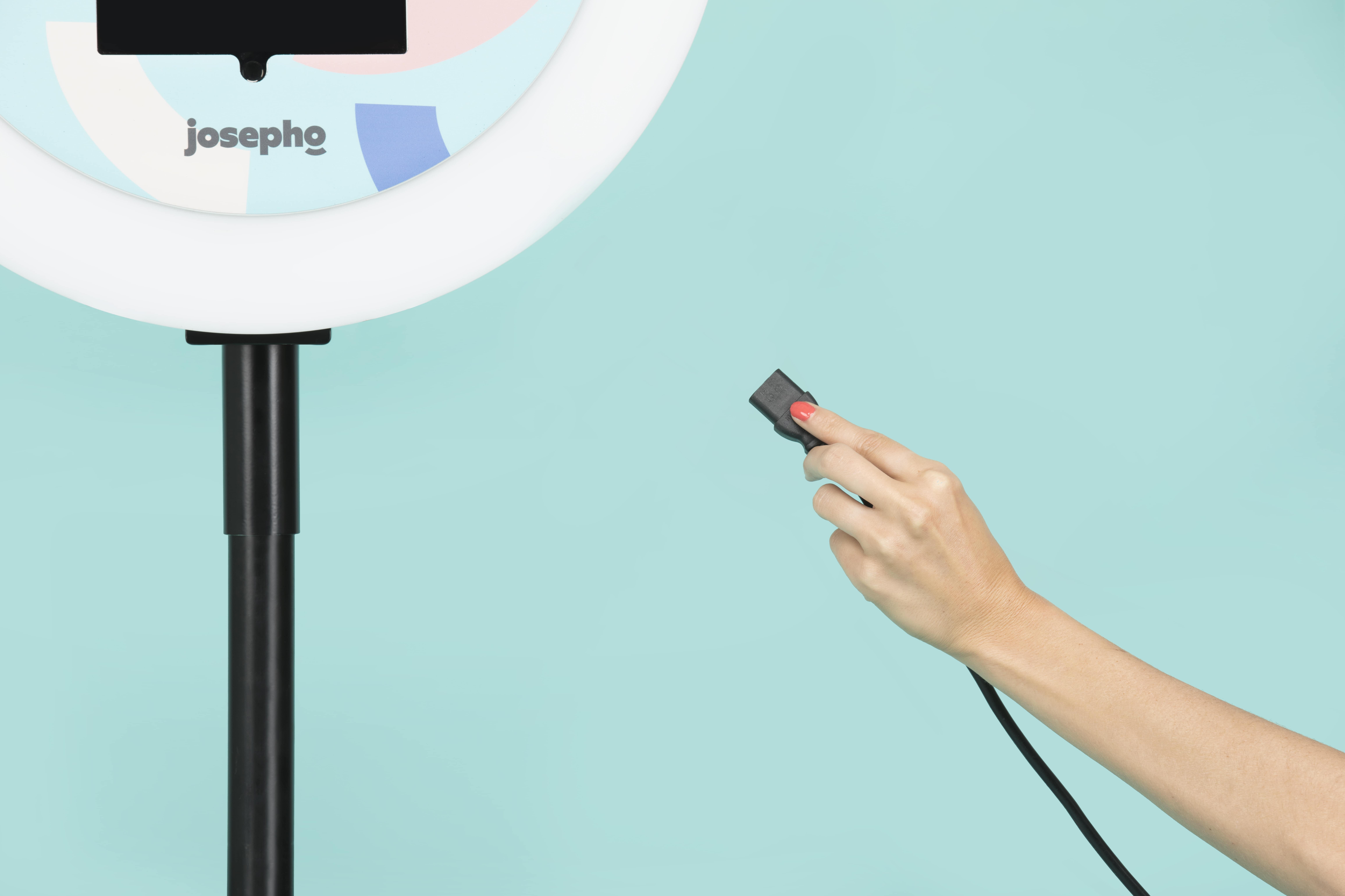 Une main est en train de brancher le photobooth / photomaton Josepho