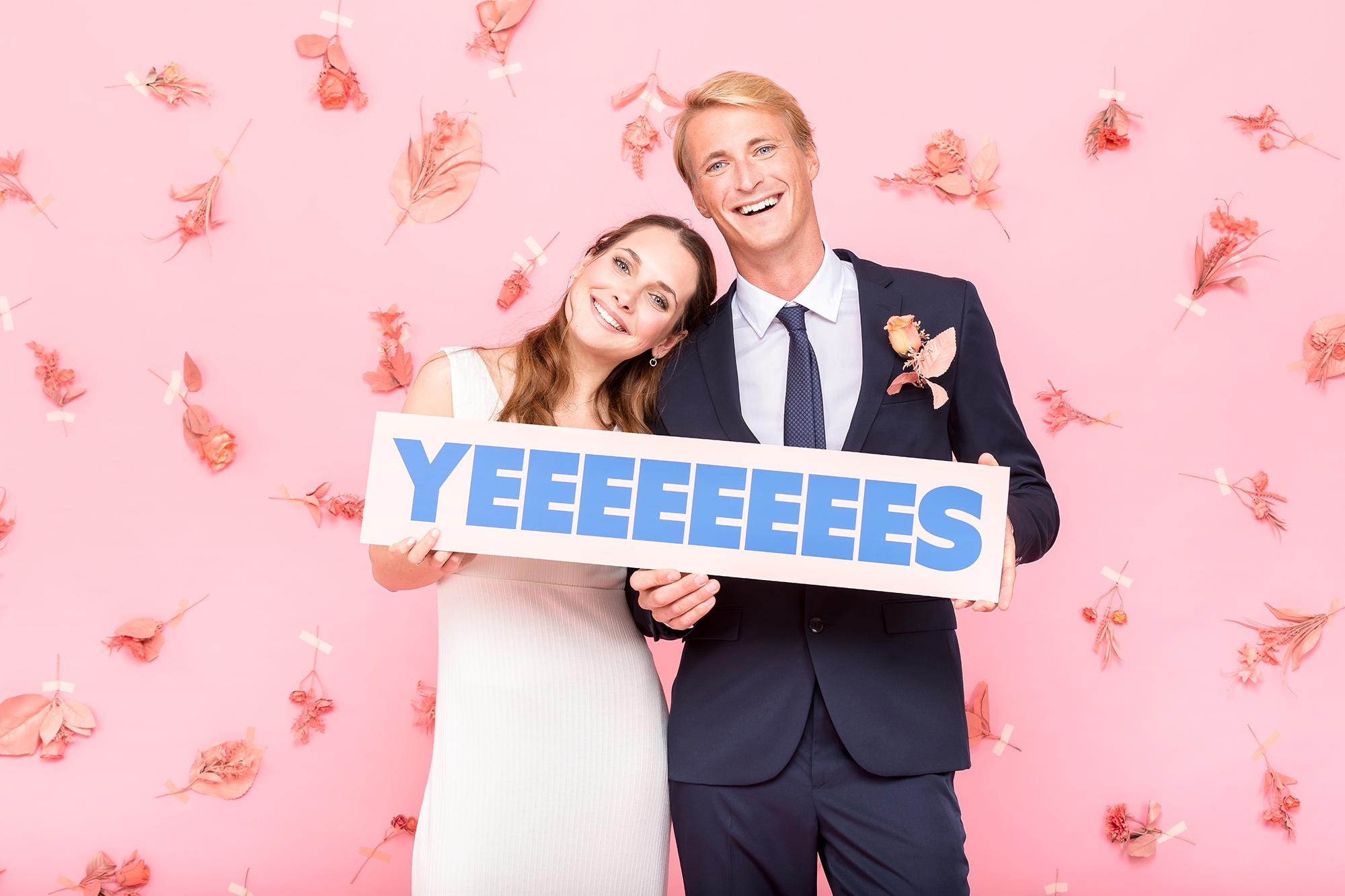 Un couple de jeunes mariés se prend en photo avec le photobooth / photomaton de Josepho