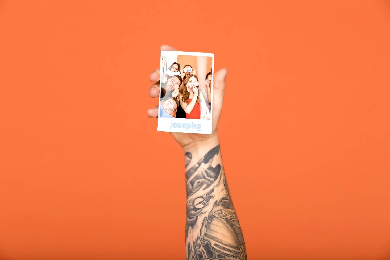 Une main d'homme tient une photo imprimée par la borne photo Josepho. Sur la photo nous voyons un groupe d'amis qui s'amusent et rient ensemble.
