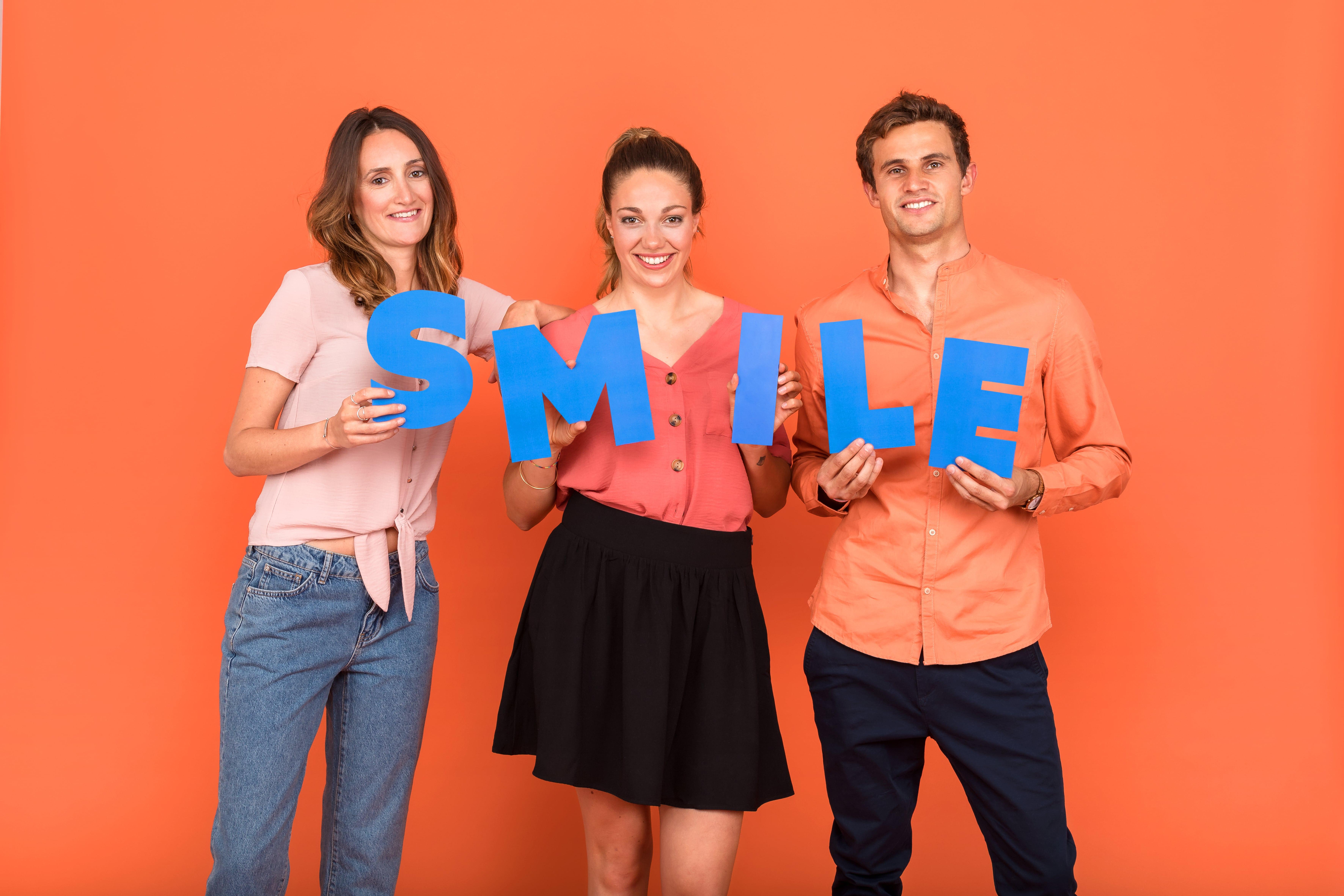 Deux femmes et un homme portent des lettres qui forment le mot SMILE qui représente une valeur de l'entreprise Josepho