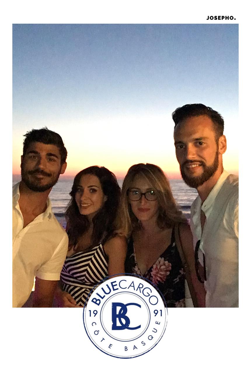 Une photo prise avec le photomaton de Josepho sur la terrasse du Blue Cargo face à la mer montre un groupe d'amis en train de sourire et se prendre en photo. Le cadre de la photo est personnalisé avec le logo du Blue Cargo.