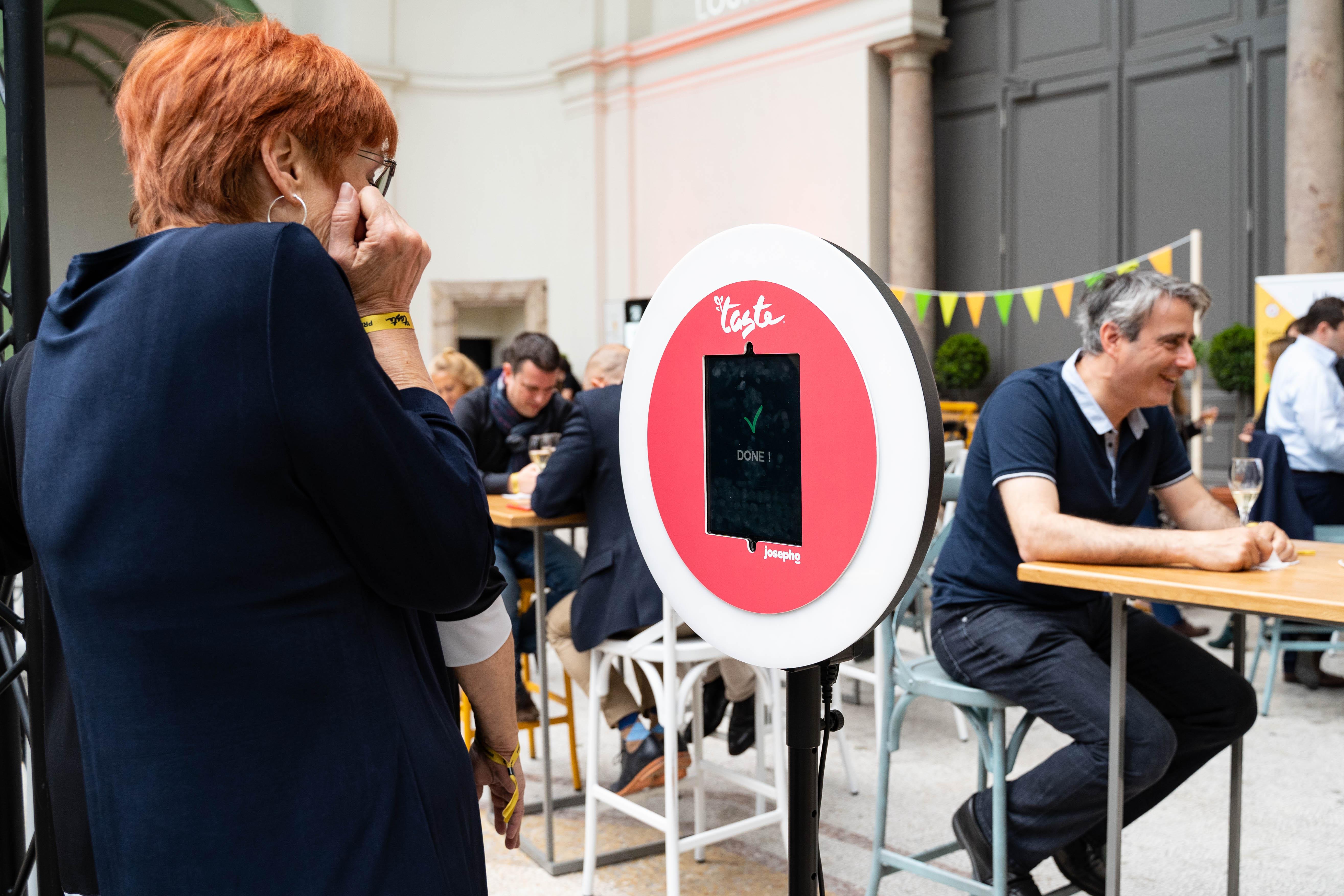Sur le salon Taste of Paris, une femme se prend en photo avec le photobooth de Josepho personnalisé avec les couleurs et le logo Taste of Paris.