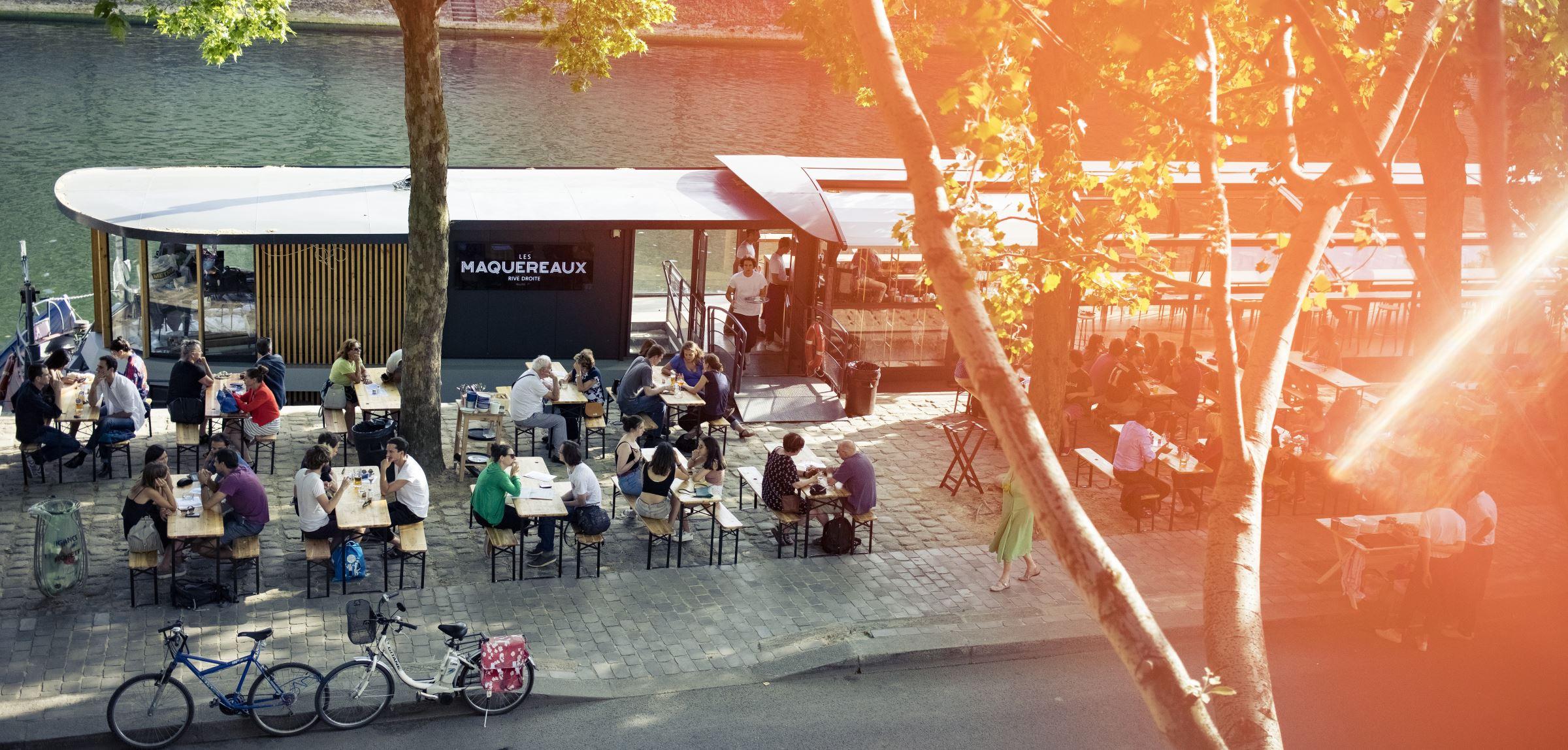 La terrasse du bar Les Maquereaux, au bord de la Seine, avec des personnes qui y boivent un verre.