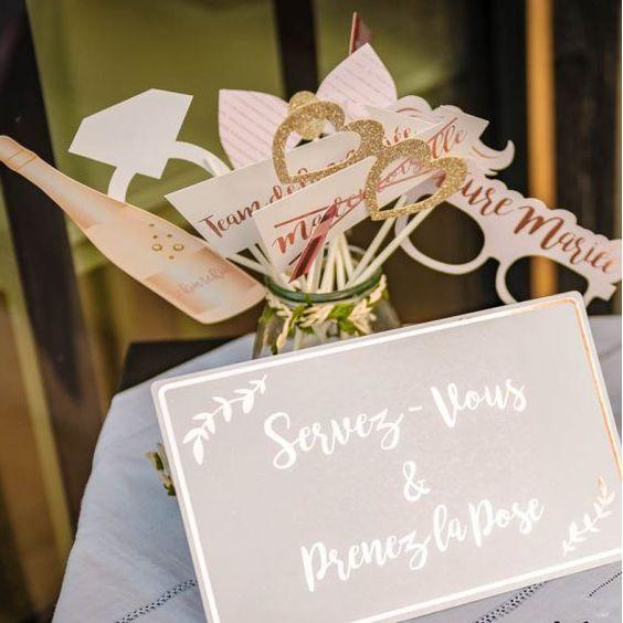 """Sur une table sont positionnés des accessoires pour prendre des photos fun avec un photomaton avec une pancarte qui dit """"Servez vous et prenez la pose""""."""