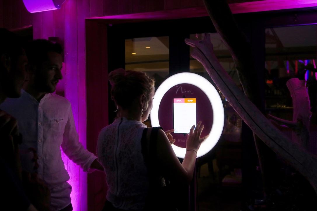 Une femme se prend en photo avec le photomaton de Josepho de nuit.