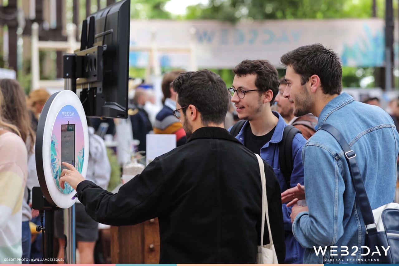 Trois amis se prennent en photo pendant le salon Web2Day avec le photobooth Josepho qui est personnalisé aux couleurs du salon Web2Day.