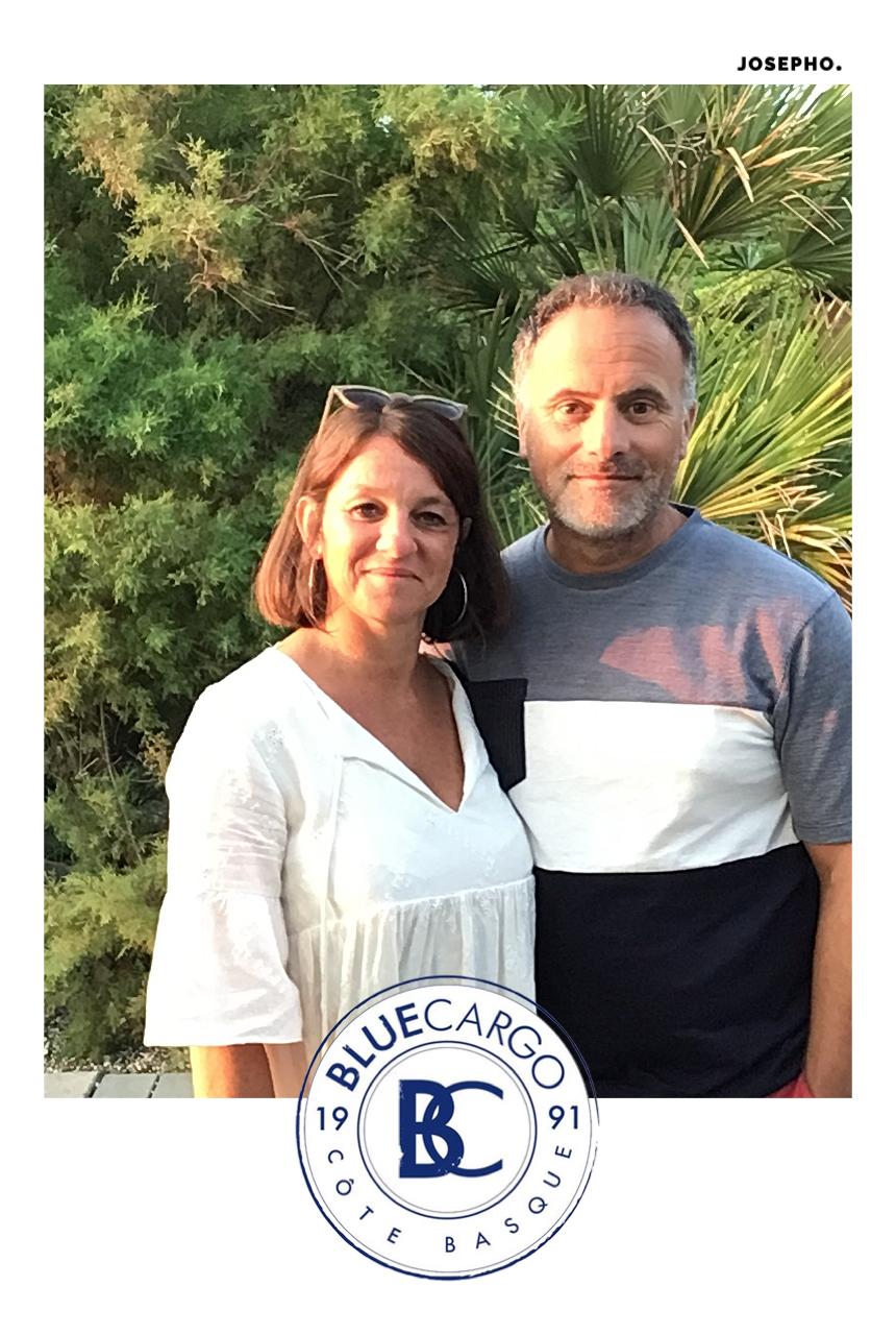 Une photo prise avec le photomaton de Josepho sur la terrasse du Blue Cargo montre un couple en train de sourire et se prendre en photo. Le cadre de la photo est personnalisé avec le logo du Blue Cargo.