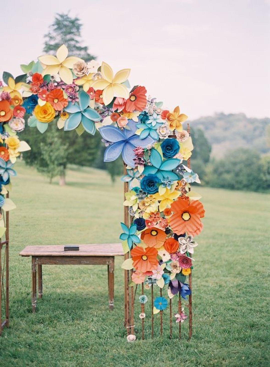 Un photocall, réalisé avec des fleurs en papier, est positionné dans un champ.