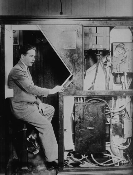 Anatol Josepho qui présente sa cabine photographique, l'ancêtre du photomaton.