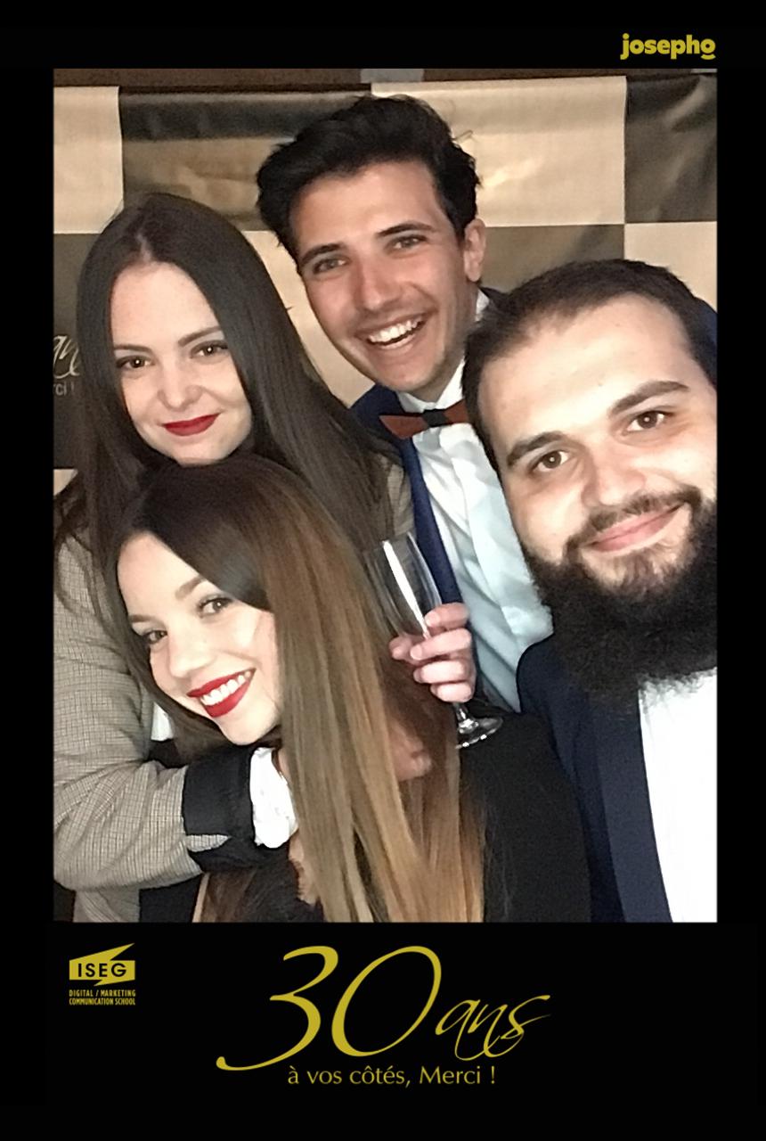 Une photo prise avec le photobooth de Josepho montre un groupe d'amis en train de s'amuser et se prendre en photo avec le photobooth de Josepho. Le cadre de la photo est personnalisé avec le logo de l'école ISEG.