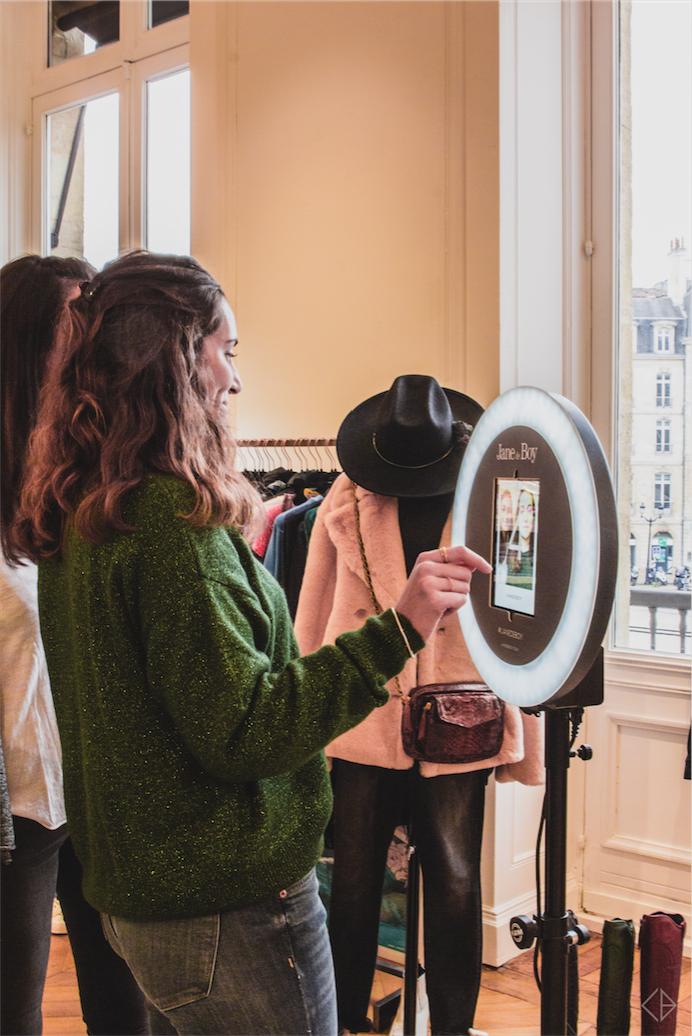 Une femme se prend en photo avec le photobooth de Josepho qui est positionné dans la boutique Jane de Boy et personnalisé avec les couleurs et le logo Jane de Boy.