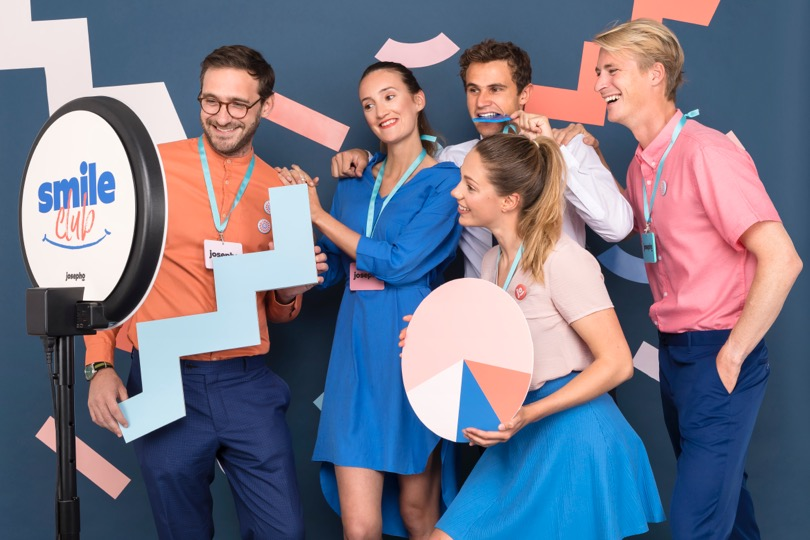 """Un groupe de 5 collègues sourit et se prend en photo devant le photobooth de Josepho qui est personnalisé avec le slogan """"Smile Club"""" de Josepho."""