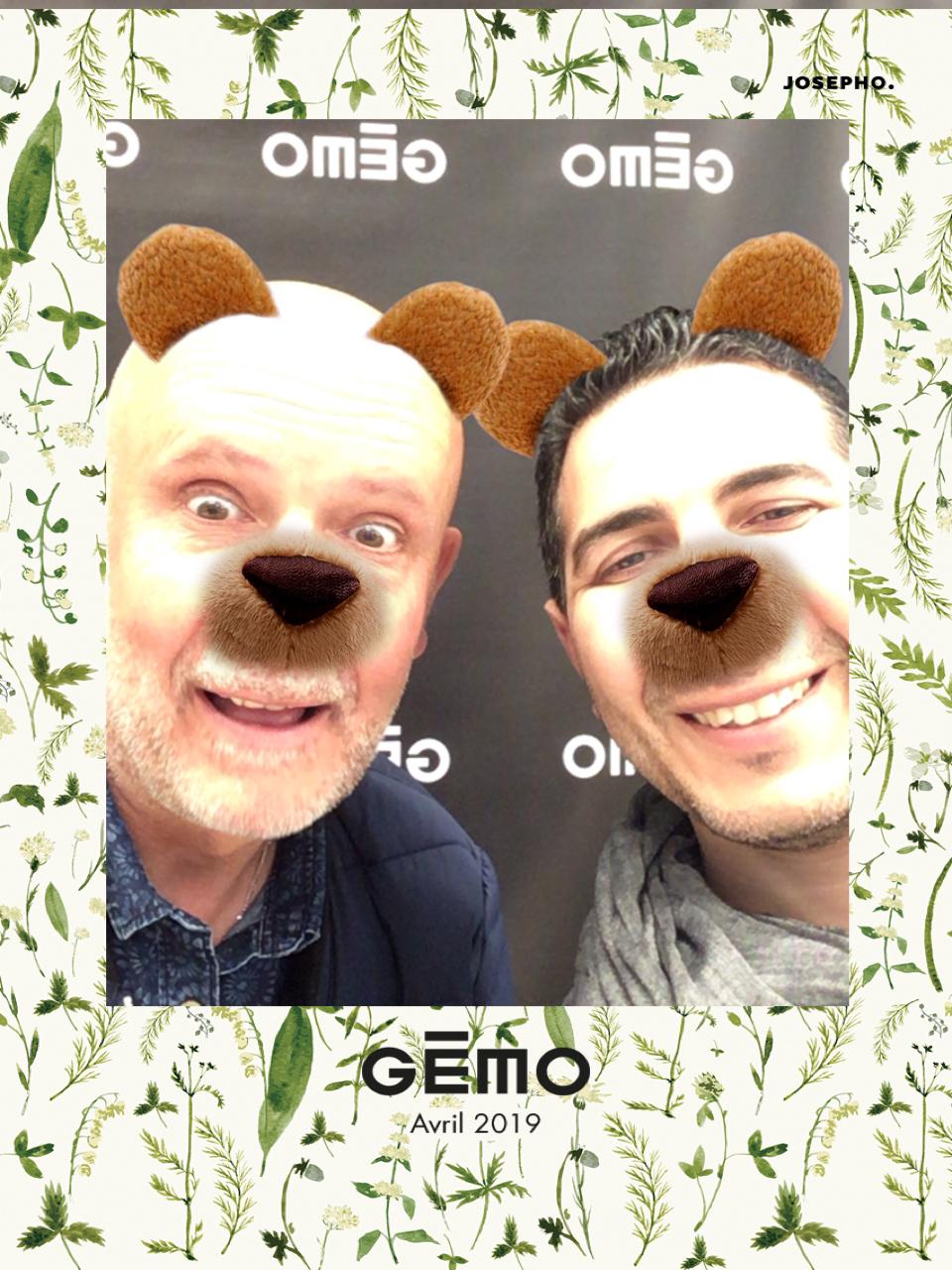 Une photo prise avec le photomaton de Josepho montre deux hommes qui sourient et qui ont un nez et des oreilles d'ours réalisés grâce à l'effet morphing du photomaton de Josepho. Le cadre de la photo est personnalisé avec le logo Gémo et la date de prise de la photo.