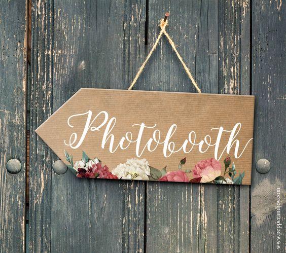 """Une pancarte où est ecrit le mot """"Photobooth"""" est attachée sur un mur en bois et indique l'endroit où se trouve le photobooth."""