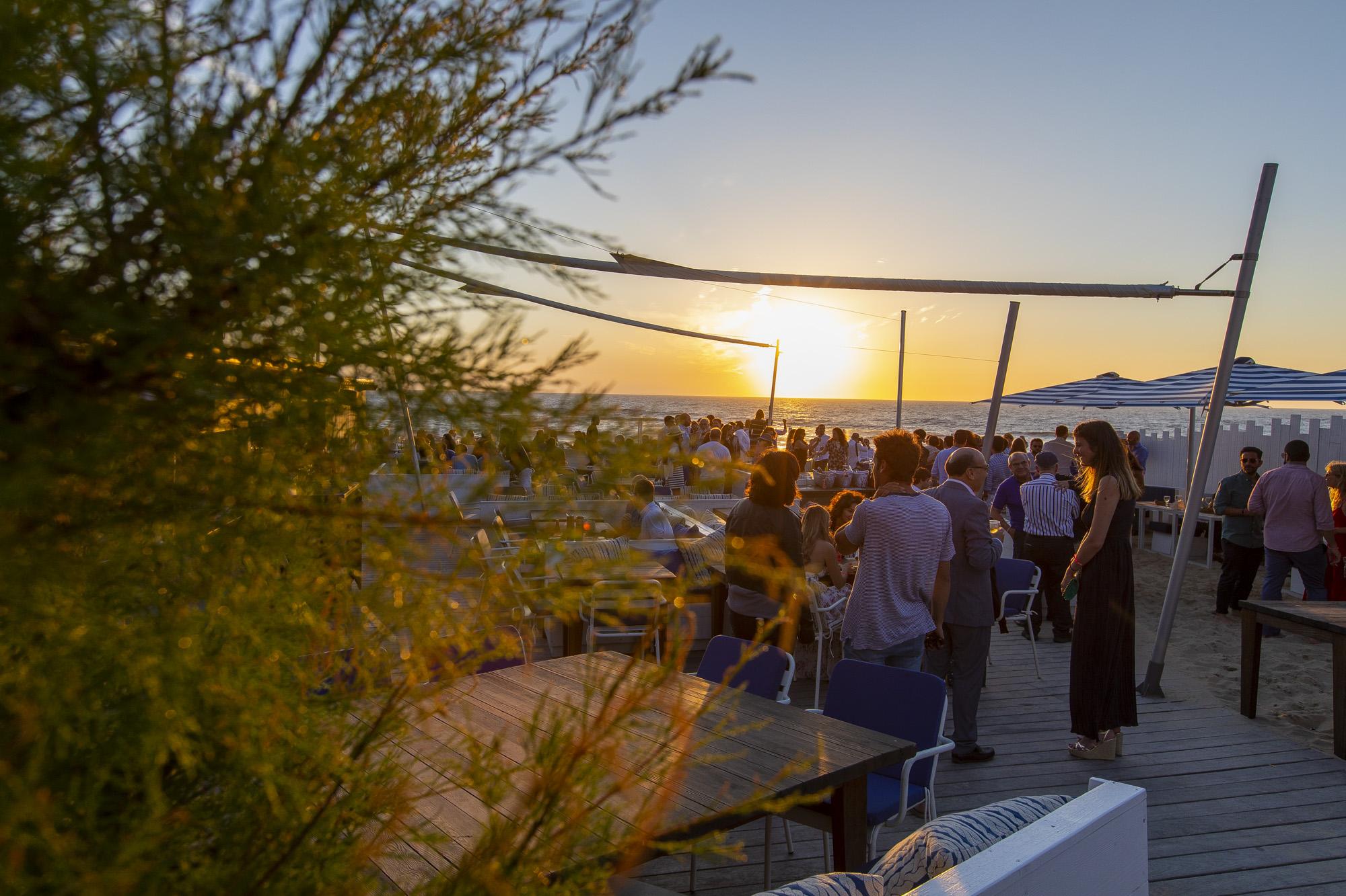 Des gens discutent et prennent un verre sur la terrasse du Blue Cargo sur le sable face à la mer au coucher du soleil.