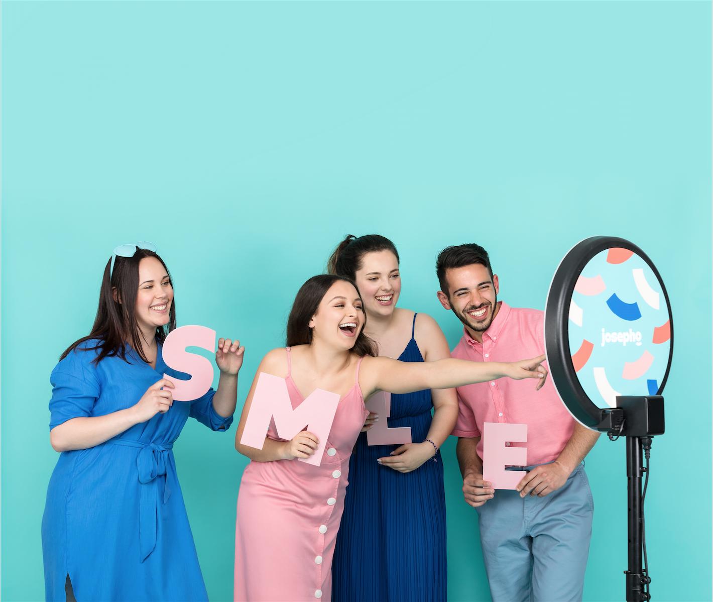 """Quatre amis se prennent en photo devant le photobooth en rigolant et en tenant chacun une lettre pour créer le mot """"Smile""""."""
