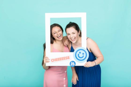 Deux collègues rient et tiennent une pancarte en forme de cadre photo autour de leur tête en train de se prendre en photo avec le photomaton Josepho.