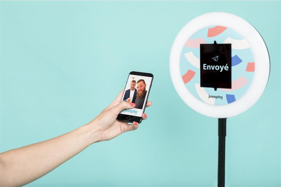 """Le photobooth de Josepho est de face avec le message """"envoyé"""" inscrit sur l'écran. Au premier plan une main tient un smartphone avec, sur son écran, la photo de deux amis prise avec le photobooth de Josepho."""