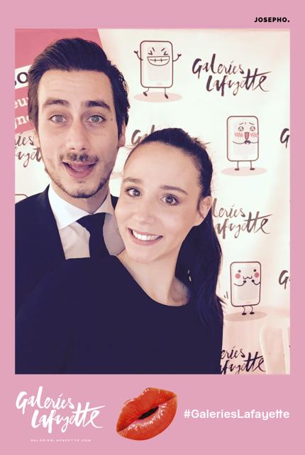 Une photo prise avec le photobooth de Josepho montre un couple en train de sourire et se prendre en photo. La cadre de la photo est personnalisé avec le logo et le hashtag Galeries Lafayette.