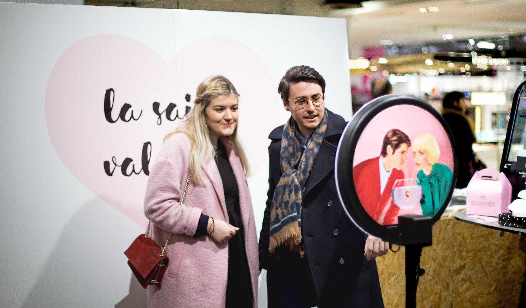 """Aux Galeries Lafayette, un couple se prend en photo avec le photobooth de Josepho devant un photocall """"La Saint Valentin""""."""