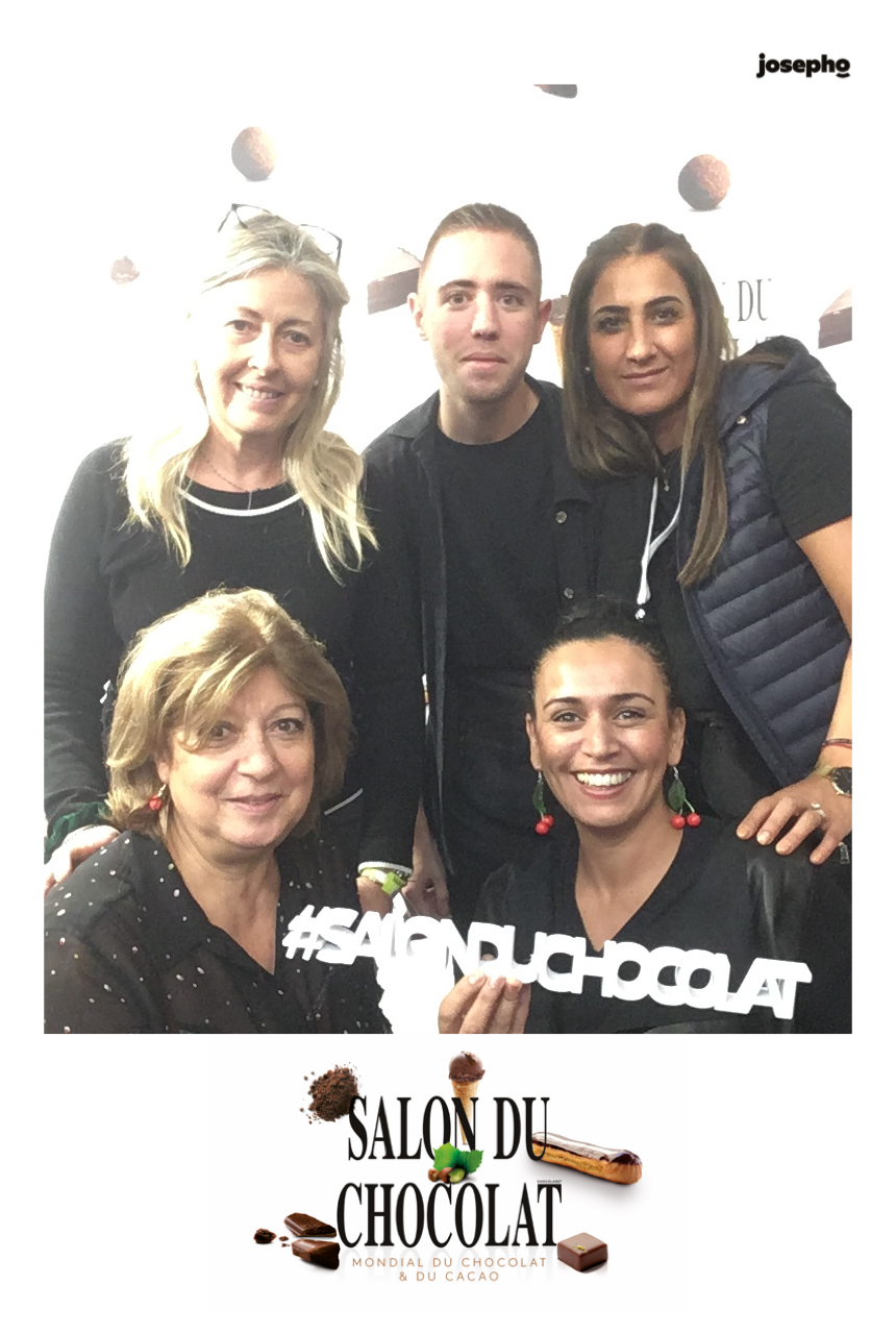 Une photo prise avec le photobooth de Josepho montre un groupe de personnes en train de sourire et se prendre en photo. Le cadre de la photo est personnalisé avec le logo du Salon du Chocolat.