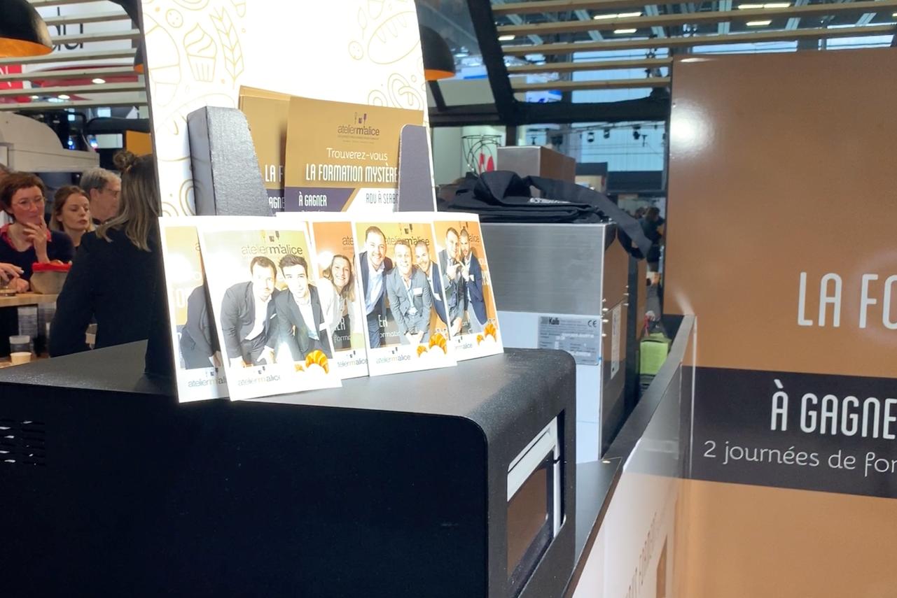Des impressions de photos prises avec le photobooth de Josepho sont mises en évidence sur le stand d'Atelier Malice au salon Serbotel