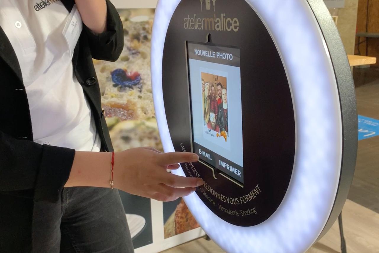 La photo d'un groupe apparait sur l'écran du photobooth de Josepho qui est personnalisé avec le logo Atelier Malice.