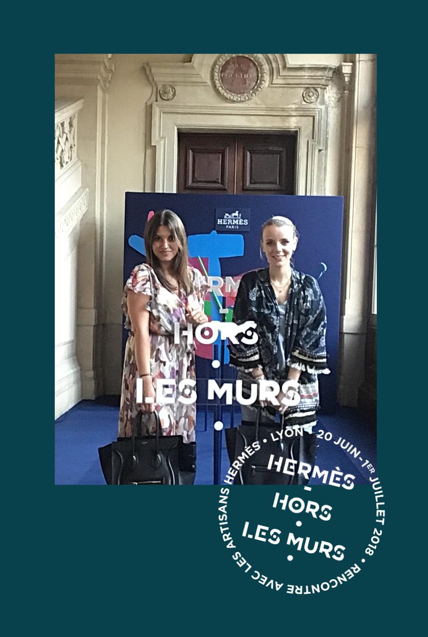 Une photo prise avec le photobooth de Josepho montre deux femmes en train de se prendre en photo devant un photocall Hermès. Le cadre de la photo est personnalisé avec les couleurs et le logo Hermès Hors Les Murs.