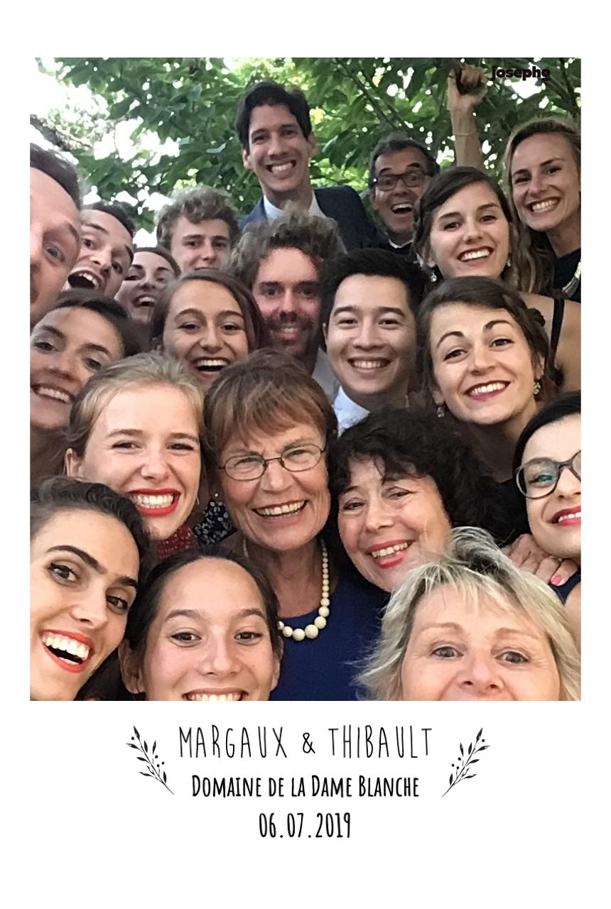 Une photo prise par le photobooth de Josepho montre un selfie de 19 personnes à un mariage. La photo est personnalisée à l'honneur des mariés avec leur prénom et la date de leur mariage