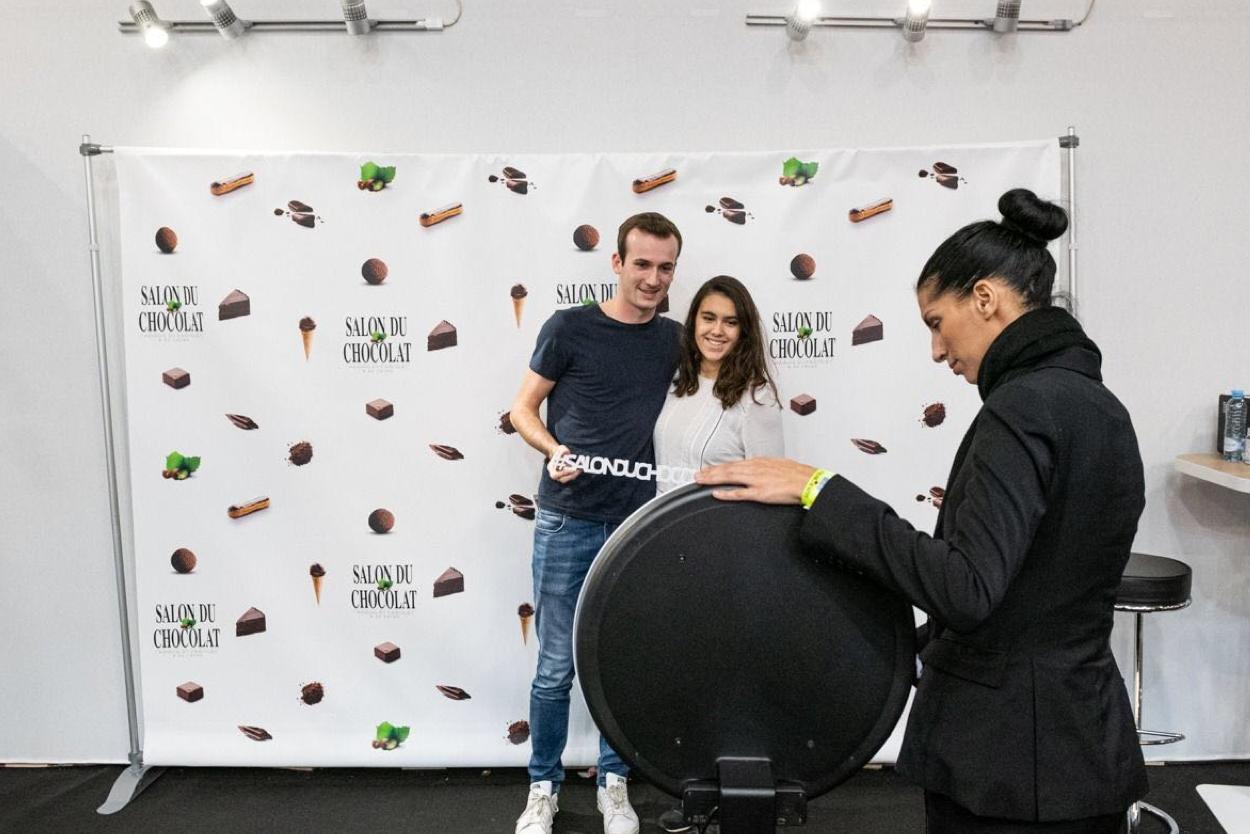 Sur la Salon du Chocolat, une hôtesse d'accueil prend en photo un couple avec le photobooth de Josepho devant un photocall aux couleurs du salon.