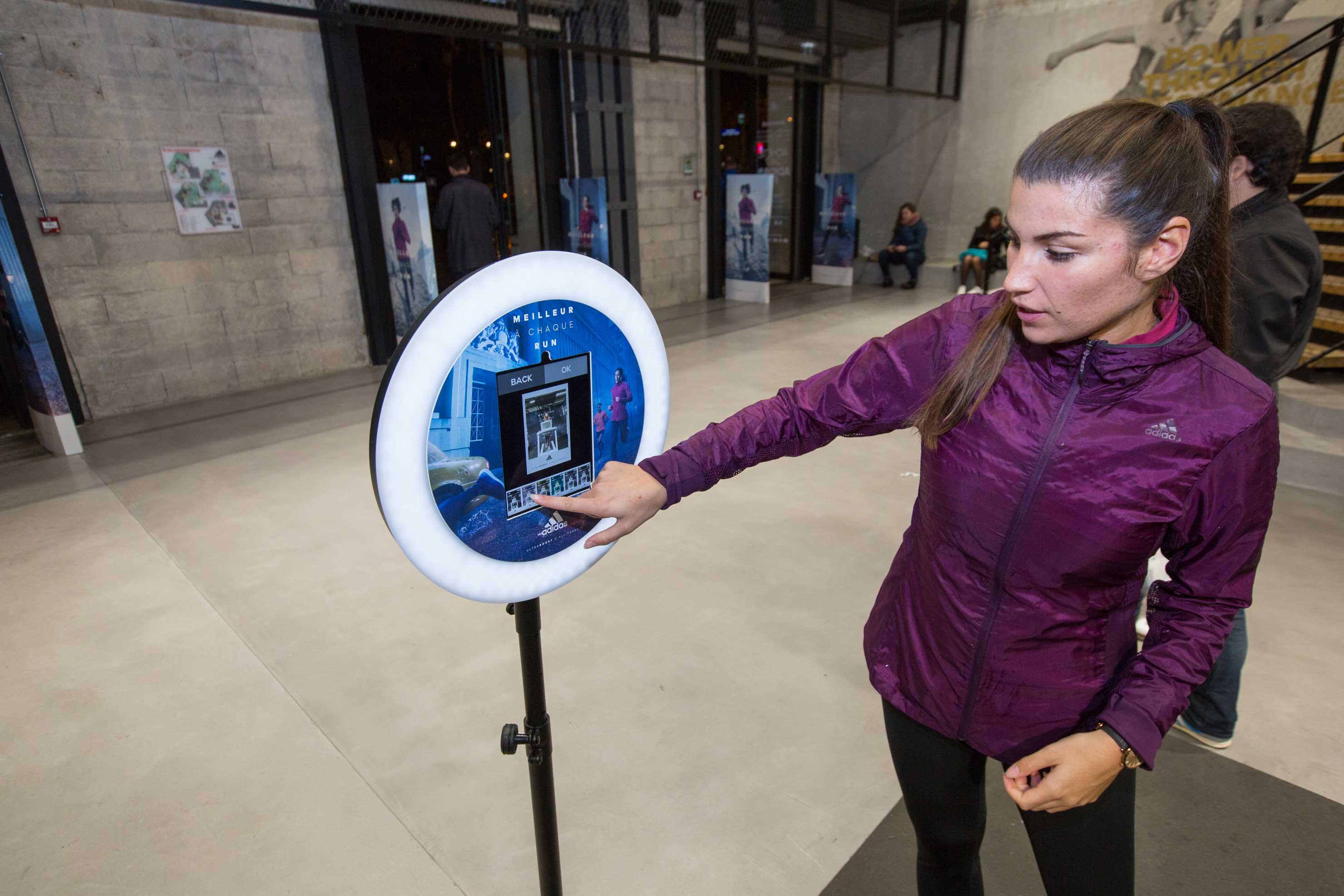 Dans un magasin Adidas, une femme pianote sur l'écran du photobooth de Josepho pour choisir le filtre de sa photo.