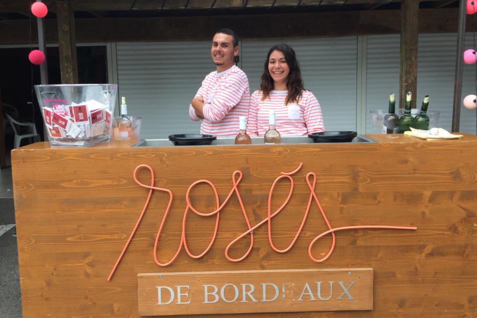 Les serveurs derrière le stand Rosés de Bordeaux prennent la pose et sourient.