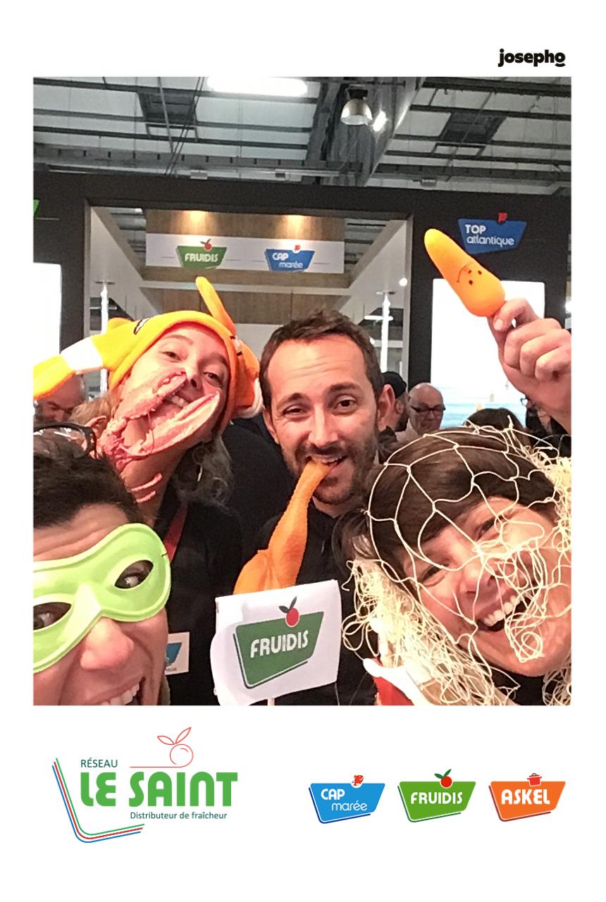 Une photo prise par le photobooth de Josepho montre un groupe de personnes s'amuser avec des accessoires et se prendre en photo. Le cadre de la photo est personnalisé.