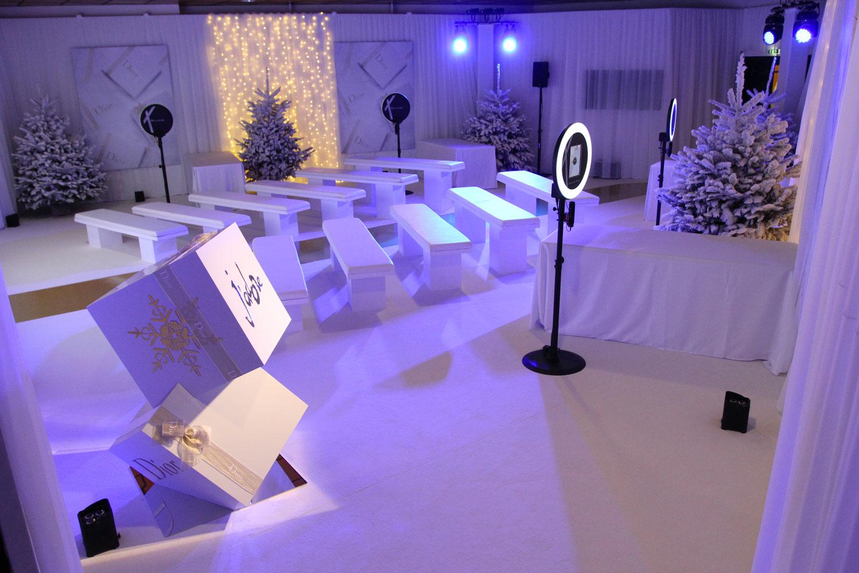Quatre photobooth de Josepho sont installés dans une salle à la décoration de Noël avec des sapins enneigés et des cadeaux géants Dior blanc et or.