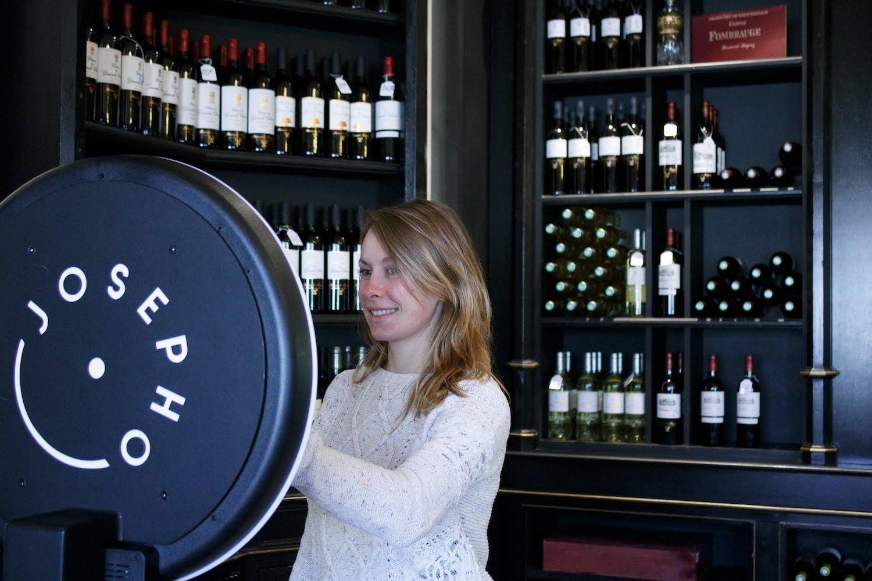 Une femme se prend en photo avec le photobooth de Josepho dans la boutique du Château Pape Clément.