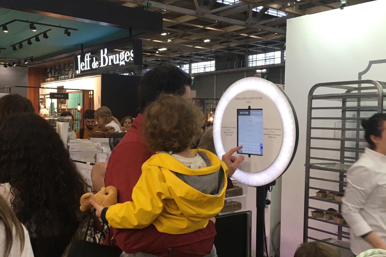 Sur le Salon du Chocolat, un père avec son enfant des les bras pianote sur l'écran du photobooth de Josepho qui est personnalisé avec le logo Philippe Conticini.