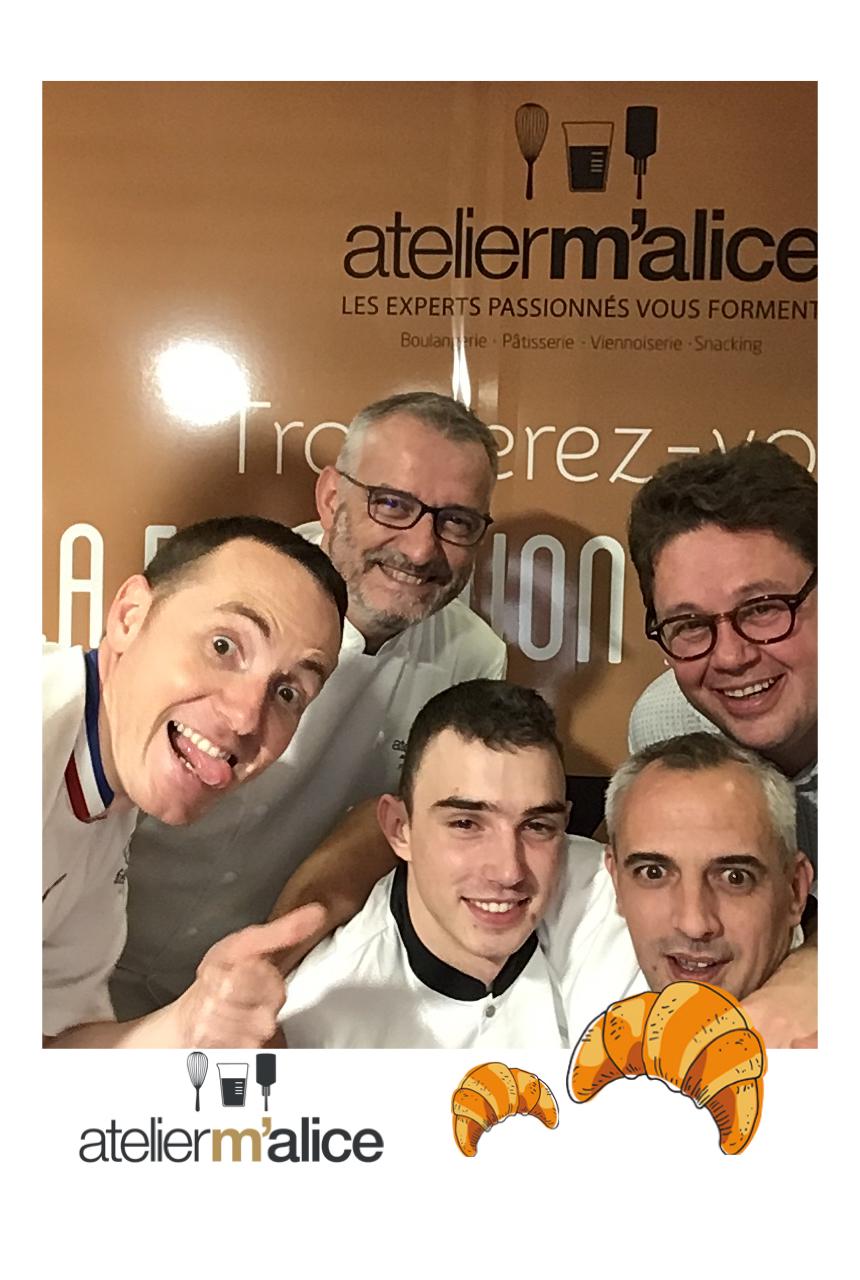 Une photo prise avec le photobooth de Josepho montre un groupe de personnes en train de sourire et de se prendre en photo. Le photocall et le cadre de la photo sont personnalisés avec les couleurs et le logo Atelier Malice.