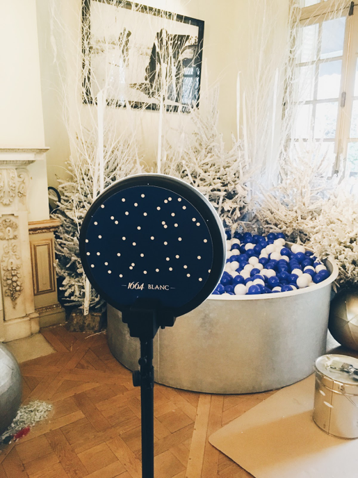 Le photobooth de Josepho est positionné devant un photocall sur le thème de Noël dans un salon d'appartement pour un événement de la marque de bière 1664. La pièce est décorée avec des sapins enneigés et un bac avec des boules bleues et blanches.