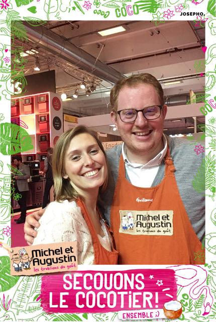 Une photo prise avec le photomaton de Josepho montre une femme et un homme en train de sourire et se prendre en photo. Le cadre de la photo est personnalisé avec le logo et les éléments de la marque Michel & Augustin.
